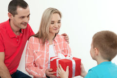 Son hiding gift to surprise mommy on mother`s day. Woman, man an. Son hiding gift to surprise mommy on mother`s day. Woman, men child hugs and kisses Royalty Free Stock Photography