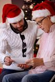Son and his father watching photo and share memory on Christmas Stock Image