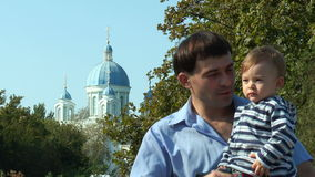 Son with his father in the background of the church stock video footage