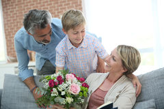 Son with his father giving flowers to his mother. Young boy giving flowers to mommy for mother's day Royalty Free Stock Photo