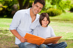 Son with his father looking at their album photo. In the park royalty free stock images