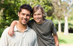 Son and his father in the park. Son and his father posing in the park Royalty Free Stock Photo