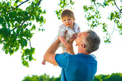 Son in his father's arms. Father and young son playing on nature. Son in his father's arms royalty free stock photography