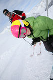 Son and his father skiing the slopes. Daddy with young boy skiing down ski slope Stock Images