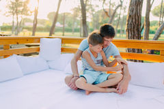 Son with his father on a wooden couch Stock Image