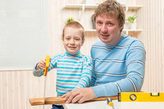 Son with his father working with tools and boards. In the garage royalty free stock photography