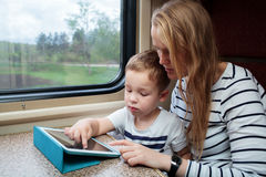 Son and his mom with tablet PC in the train. Mother and her little son using touchpad sitting by the window in the train stock image