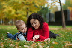 Son with his mother in the park. Son with his mother in a park in autumn Royalty Free Stock Photos