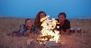 The son and his parents roast marshmallow on sticks. Family camping on the beach in the evening. A family. stock footage