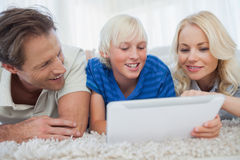 Son and his parents using a tablet. Lying on a carpet Royalty Free Stock Image