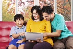 Son and his parents using tablet. Portrait of little boy and his parents using digital tablet at home in autumn day Royalty Free Stock Photos