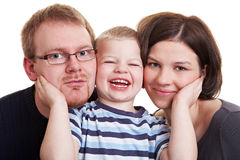 Son holding cheeks of parents. Happy little boy pressing his parents cheeks against his own Stock Image