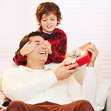 Son holding eyes of father closed. Son holding eyes of father with gift closed at christmas Stock Image