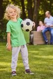 Son holding football ball. Sweet little son holding a football ball in the garden Royalty Free Stock Image