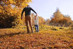 Son holding hands his fther. In sunny autumn day Royalty Free Stock Photography