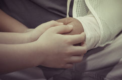 Son holding his father's hand who has an accident Royalty Free Stock Photo