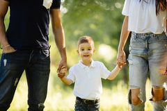 Son holding mother and father for hands in park. Son holding mother and father for hands royalty free stock image
