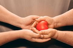 Son holding mother hand with red heart symbol inside. For care expression stock photography