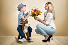 The son on the horse, gives a basket of flowers beloved mother.Little Prince on horseback.Spring ,women`s day. Son rode on horseback to his beloved mother.son royalty free stock photo