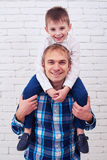 Son hugging dad around the neck while posing against white brick. Mid shot of son hugging dad around the neck while posing against white brick background in Stock Photos