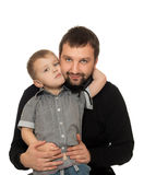Son hugging dad. A small blond boy in a grey shirt and jeans sitting on his daddy's lap and hugging dad's neck.Close-up - Isolated on white background Royalty Free Stock Photos