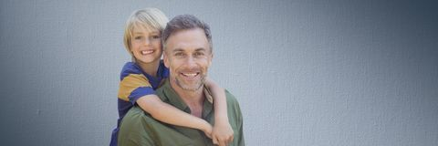 Son hugging father against navy background Stock Photo