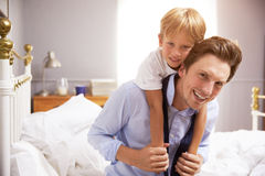 Son Hugging Father As He Gets Dressed For Work Stock Photography