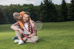 Son hugging father after playing badminton together on green lawn. Little son hugging father after playing badminton together on green lawn Stock Photos