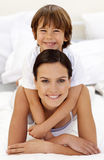 Son hugging his mother in bed. Happy son hugging his mother in bed royalty free stock photo