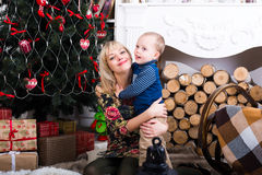 Son hugging his mother. Near Christmas tree Royalty Free Stock Photos