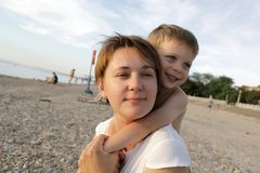 Son hugging his mother. On the beach Stock Photo