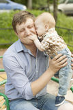 Son hugging and kissing his father. Happy playful son hugging and kissing his laughing father Stock Photos