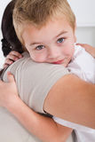 Son hugging mother. A cute young blond son hugging his mother and smiling Royalty Free Stock Photo