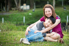 Son hugging mother Asian family. In the park Stock Images