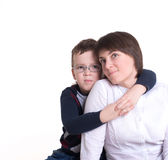 Son hugging mother. Son in glasses hugging her mother's shoulders royalty free stock images