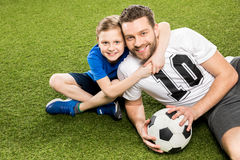 Son hugging smiling father while lying on grass Royalty Free Stock Photo