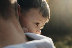 Son hugs father lying on the shoulder. The sun shines on his face. A litle boy in plaid shirt royalty free stock photography