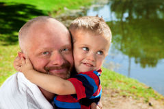 Son Hugs Father's Head. A young boy hugs his father's head by a pond in the park Royalty Free Stock Images