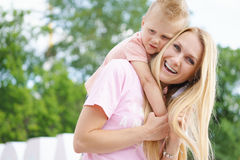 The son hugs mom at outdoor. Happy family. Young son hugs mom at outdoor royalty free stock image