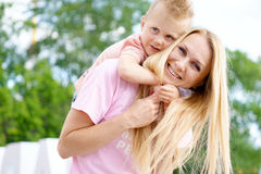 The son hugs mom at outdoor. Happy family. Young son hugs mom at outdoor stock photography