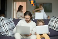 Father and son using laptops sitting on sofa at home Stock Photo