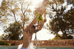 Son Jumping From Father`s Shoulders In Outdoor Pool Stock Photography