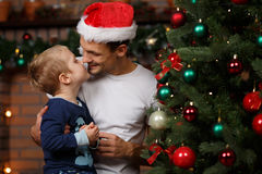 Son kisses daddy at tree. Son kisses daddy at Christmas tree in new year Royalty Free Stock Photography