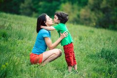 The son kisses his mother. The boy kisses his mother. A women is hugging her son. Mother and child spend time together in nature. The kid with the parent is stock images