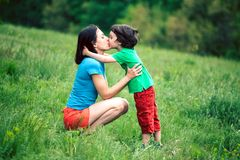 The son kisses his mother. The boy kisses his mother. A women is hugging her son. Mother and child spend time together in nature. The kid with the parent is Stock Photos