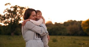 The son kisses his mother sitting at sunset in a field hugging and loving mother. Mother`s day. The son kisses his mother sitting at sunset in a field hugging stock video