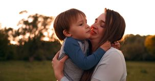The son kisses his mother sitting at sunset in a field hugging and loving mother. Mother`s day. The son kisses his mother sitting at sunset in a field hugging stock video footage