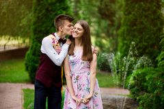 Son kisses, hugs his mom in summer day, outdoors. Young mother and her adult child having fun together. Mothers Day concept. stock images