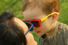 The son kisses and hugs his mom in sunglasses outdoors. Stock Photos