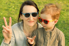The son kisses and hugs his mom in sunglasses outdoors. Mother and her child having fun together. Little kid express the love to his mommy Royalty Free Stock Images